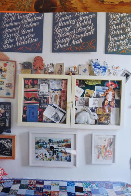 framed artworks above a bed covered with a vintage patchwork quilt